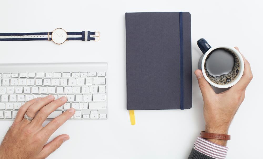 Homem a segurar chávena de café numa mesa com um teclado, um relógio e um bloco de notas
