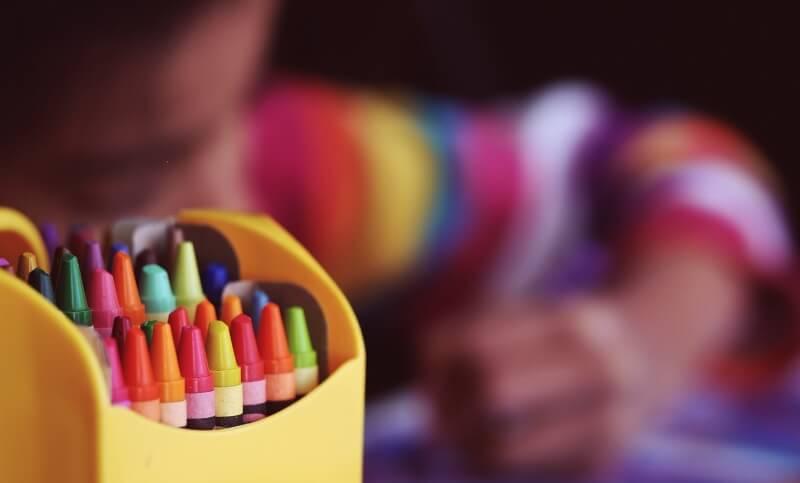 Criança a pintar com lápis de cera