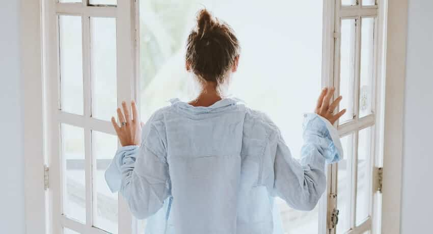 Mulher a abrir uma janela